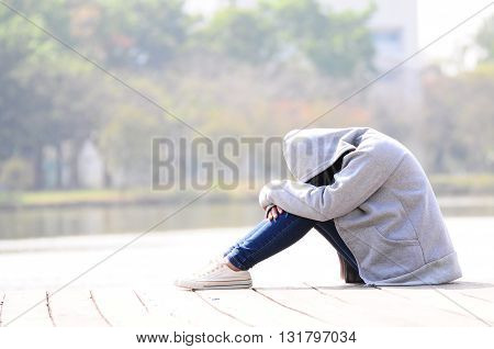 Sad woman hug her knee in the park