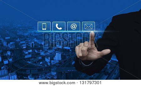 Businessman pressing telephone mobile phone at and email buttons over city tower and street blue tone background Customer support concept