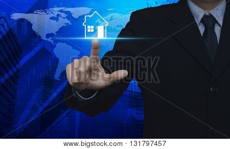 Businessman pressing house icon over map and city tower Real estate concept Elements of this image furnished by NASA
