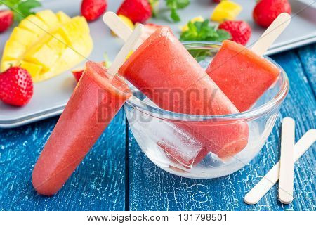 Homemade strawberry-mango popsicles on a wooden background