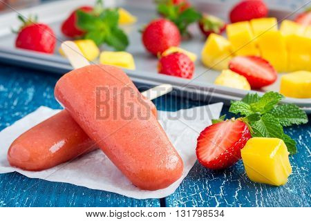 Homemade strawberry-mango popsicles on a wooden table