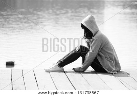 Depressed woman is sitting near the river