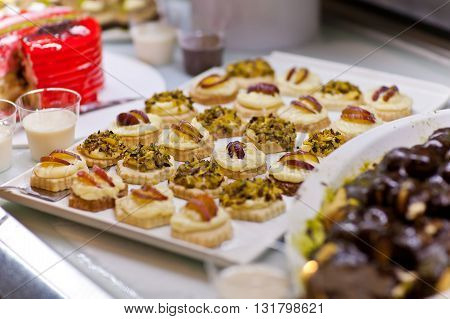 Pastries with fruit and pistachios on the buffet table.