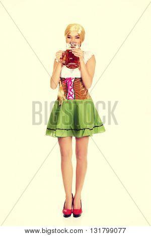 Beautiful bavarian woman drinking beer.