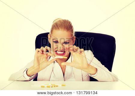 Angry business woman sitting behind the desk and breaking down cigarette