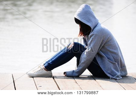 Young Woman in Despair Sitting Near River