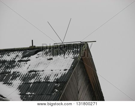 There is the roof with slate of the terrible house and broken broadcast antenna on the roof in winter