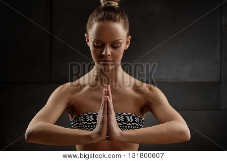Young woman practicing yoga in prayer position.