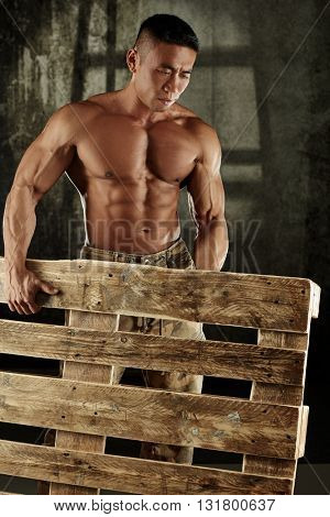 Muscular asian man holding pallet with bare upper body.