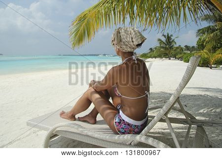 Womanl on a sun lounger under a palm tree in the Maldivian beach
