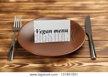 Brown plate on a brown wooden table, vegan menu