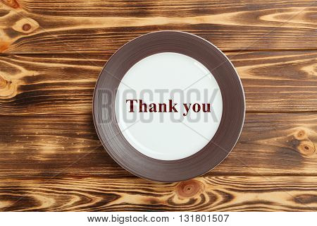 Empty brown plate on a brown wooden table, thank you