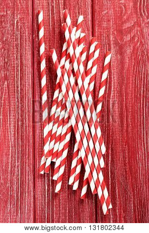 Striped Drink Straws On A Red Wooden Background