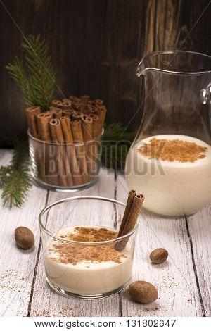Winter warm milk drink eggnog with cinnamon and nutmeg. Selective focus