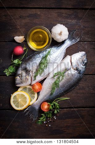 Raw dorada with ingredients on rustic background