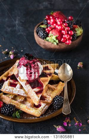Sweet waffles and ice cream on rustic background