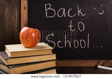 Back to school concept. Blackboard with a chalk, old books, apple. Toned image