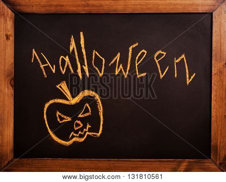 Halloween concept: pumpkin drawn on black chalkboard. Vintage style