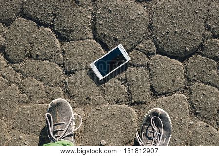 Phone with broken screen on asphalt. Someone dropped device.