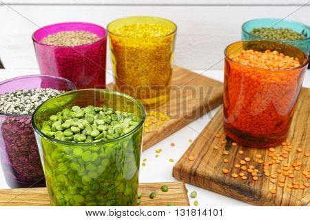 Multicolored clear glasses with various legumes ( green peas red lentils canadian lentils indian lentils black lentils green lentils green mung beans) on olive wood background