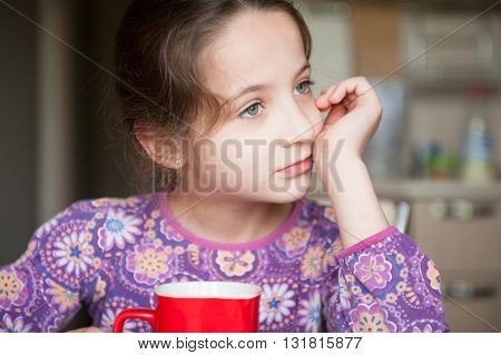 beautiful girl sitting in the kitchen with cup of tea waiting to eat dreaming