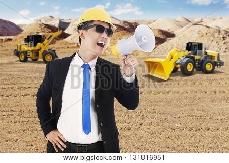 Male contractor using a megaphone for yelling with an excavator and backhoe on the background