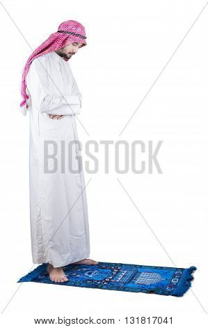 Portrait of a young devout Arabic man praying in the studio with a carpet isolated on white background