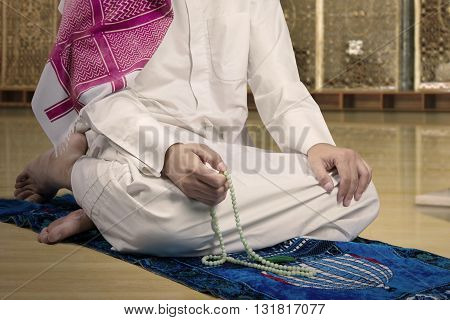 Close up of devout muslim person wearing islamic clothes and using beads to dhikr in the mosque