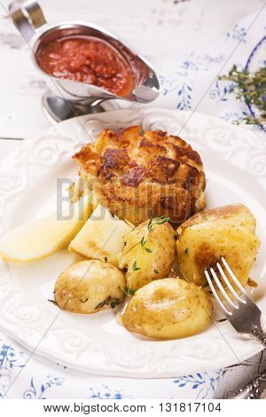 Delicious dinner: baked potatoes with thyme and cutlets, served with spicy sauce