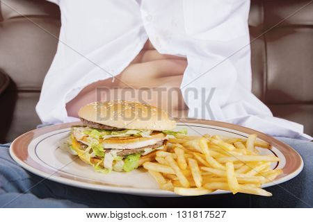 Close up of a plate of cheeseburger and french fries with potbelly of a little boy sits on the sofa