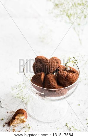 Handmade candies Tiramisu in eart shape on glass plate. Valentine's Day and Mother's Day concept with copy space. Top view.