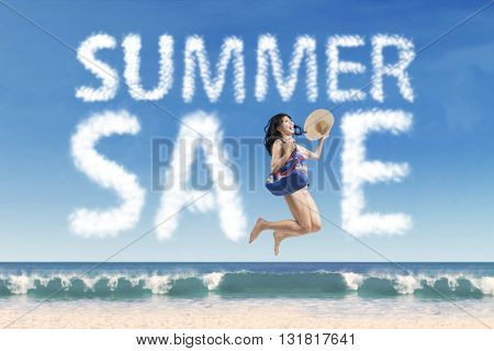 Attractive young woman carrying handbag while wearing bikini and jumping under summer sale cloud at beach