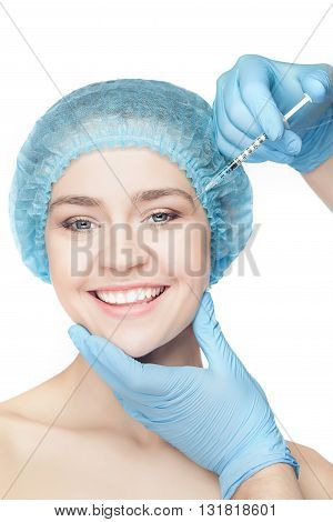 Attractive happy woman at plastic surgery with syringe in her face on white background