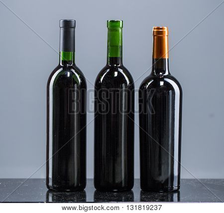 Set of white rose and red wine bottles.isolated on grey background.