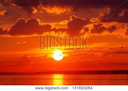 Bright red sunset over the sea with clouds