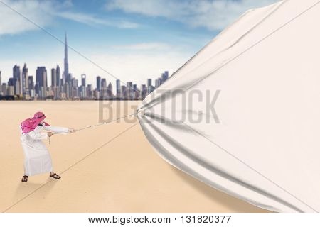 Young middle eastern man wearing headscarf and pulling a big banner outdoors