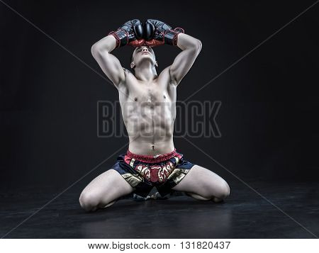 Muscular caucasian muay thai fighter isolated on black background