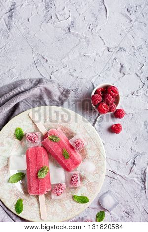 Homemade raspberry popsicles on plate with ice and berries. Summer food concept with copy space for text. Top view.