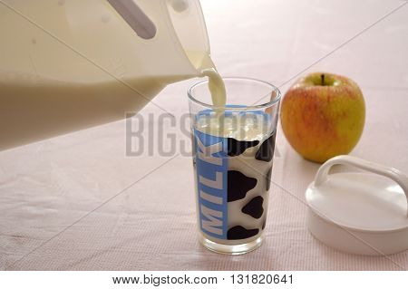 Person empty milk in glass fresh apple is at the table