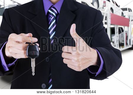 Businessman hands showing a car key and thumb up with trailer truck background