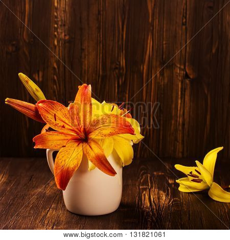Bunch of orange and yellow lilly flowers on vintage wooden dark table. Square image