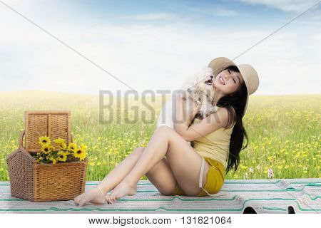 Portrait of pretty Asian girl hugging a maltese dog while sitting on the mat at the meadow