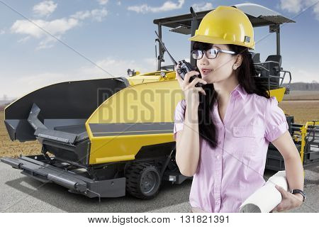 Female supervisor talking on the walkie talkie with asphalt machine on the road