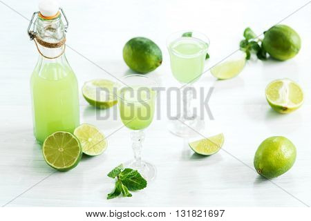 Home lime liquor in a glass and fresh lemons and limes on the old wooden background in rustic style, selective focus