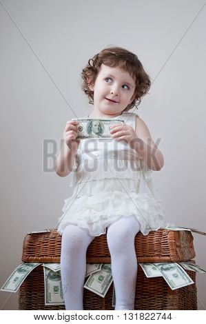 Little curly girl in dress sitting on the box with dollars and keep the dollar in the hands
