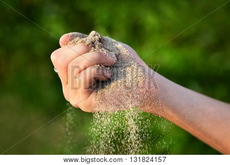 Sand in the Hand on the Nature Background closeup