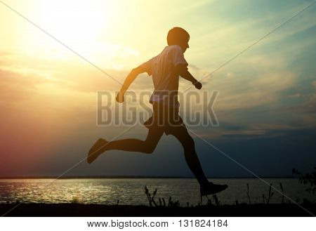 Toned Photo of Silhouette of the Man running on the Sunset Background