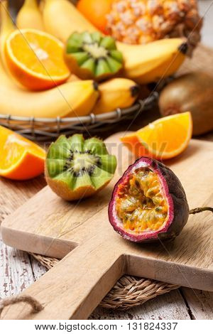 sliced passion fruit and tropical fruits in assortment: bananas kiwi pineapple orange