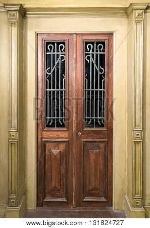 Vintage wooden brown door with glass and metal ornate grid