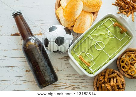 Selection of party food for watching football championship, soccer field dip, top view
